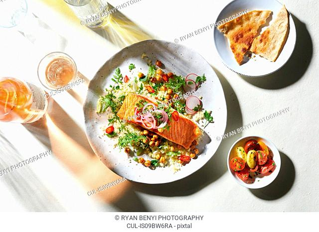 Plate of salmon and salad with pitta bread, overhead view