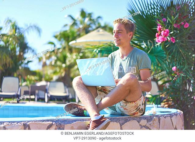 young man with laptop computer sitting in holiday destination