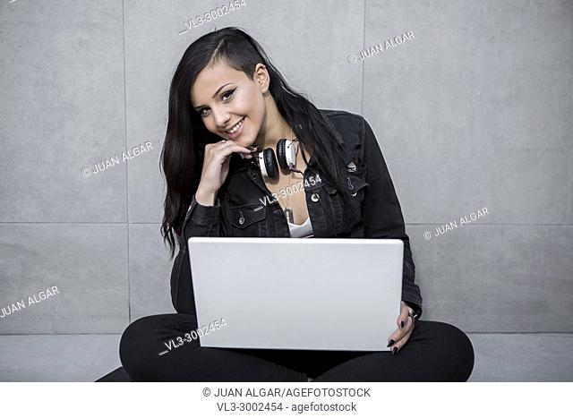 Cheerful casual young woman looking at camera and sitting with laptop
