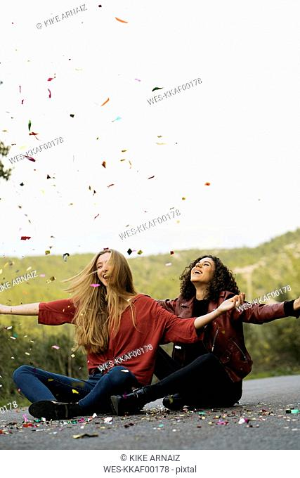 Two best friends sitting on country road throwing confetti in the air