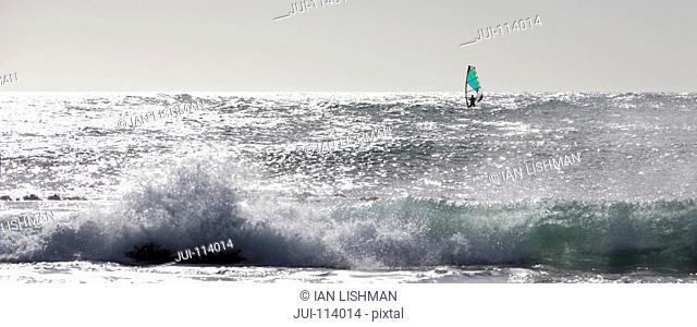 Windsurfer windsurfing in distance on sunny windy ocean