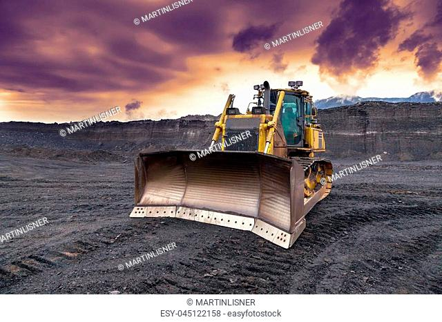 The bulldozer working in coal mines. Sunset sky