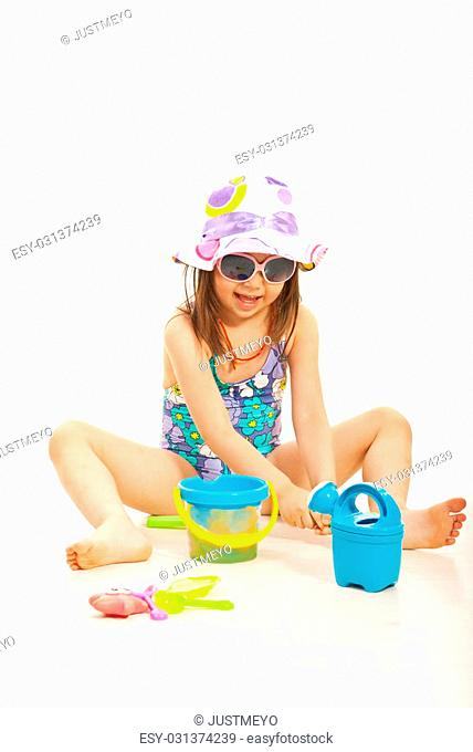 Cheerful girl playing with beach toys isolated on white background