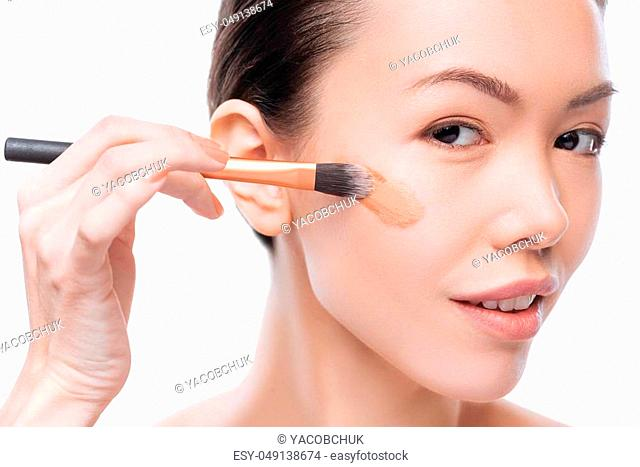 Looking natural. Happy positive beautiful woman having a make up brush in her hands and applying liquid foundation while putting on make up