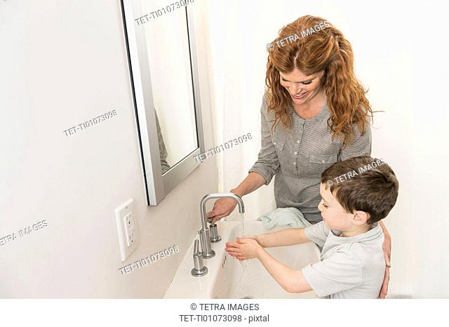 son (6-7) and mother washing hands