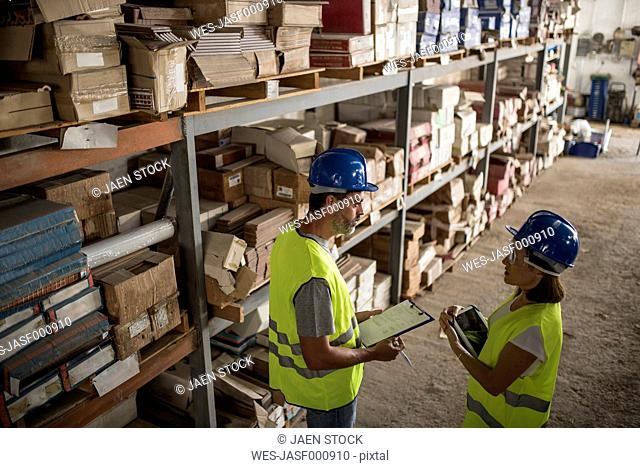 Colleagues taking stock in warehouse of construction company