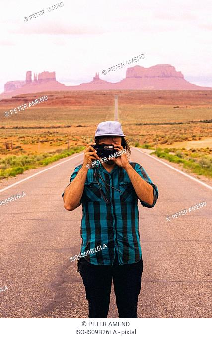 Young man taking photographs from road, Monument Valley, Arizona, USA