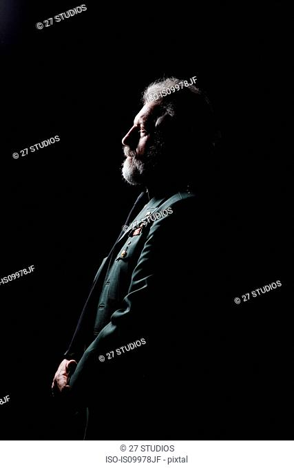 Senior man wearing military uniform against black background