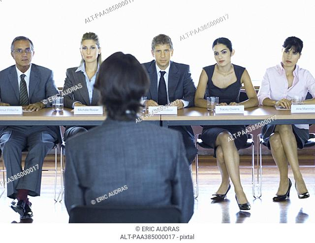 Executives sitting at conference table, looking at man in foreground