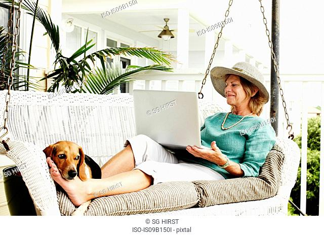 Senior woman relaxing on outdoors swing chair, using laptop, dog resting by her feet