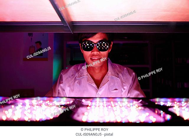 Technician wearing protective goggles in LED factory