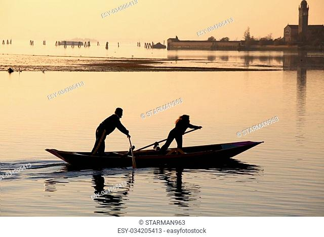 Venice sunset silhouette of couple rowing