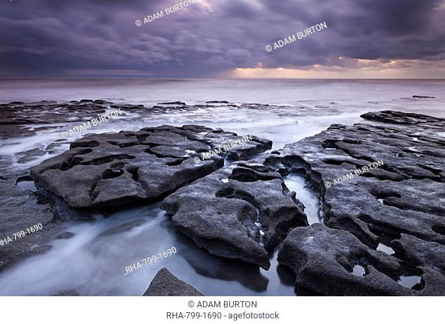 Waves rush around eroded rock ledges at Southerndown on the Glamorgan Heritage Coast, Wales, United Kingdom, Europe