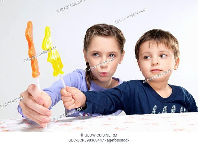 Boy and his sister showing candies