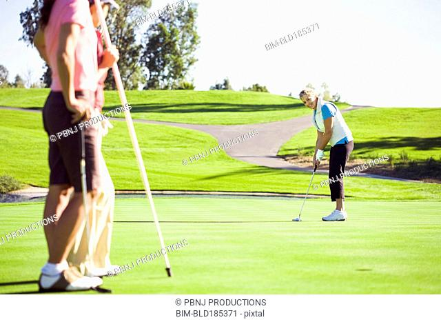 Women putting on green at golf course