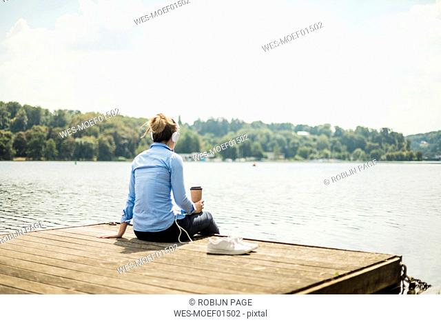 Woman sitting on jetty at a lake with headphones and takeaway coffee