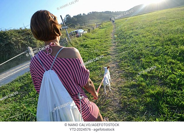 Young woman walks with her small dog in the fields of Niembro, Asturias, Spain