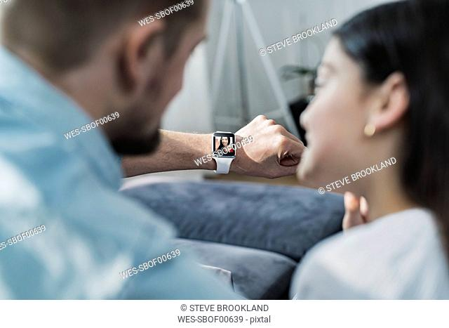 Daughter and father looking at smartwatch with mother waving at them