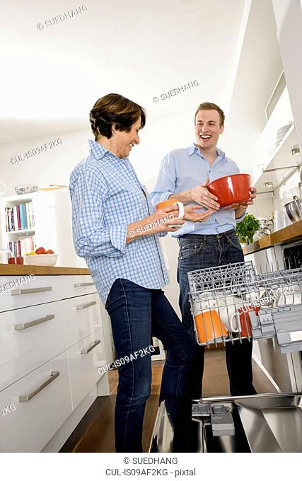 Adult grandson helping grandmother in kitchen