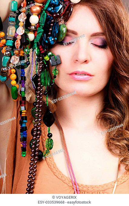 Pretty young woman holding many plentiful of precious jewelry necklaces beads. Portrait of gorgeous fashion girl in studio on gray