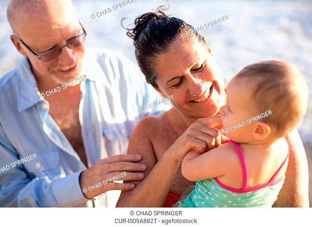 Grandparents holding granddaughter by sea, St Maarten, Netherlands
