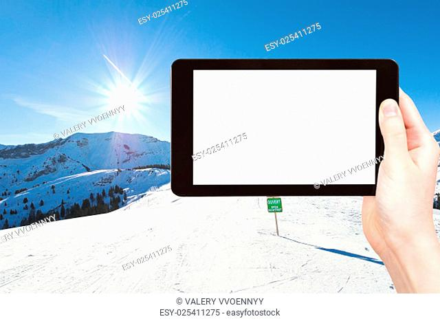 travel concept - tourist photograph skiing tracks on Alps mountains in Portes du Soleil region, Morzine - Avoriaz, France on tablet pc with cut out screen with...