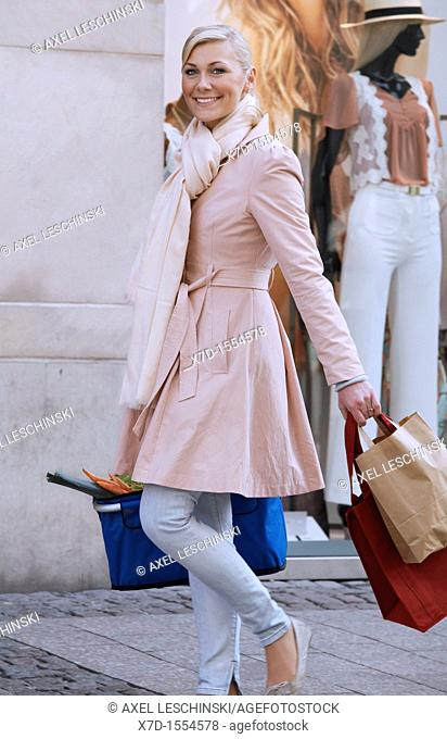 woman goes shopping in the city and have a bag fuel of fresh vegables