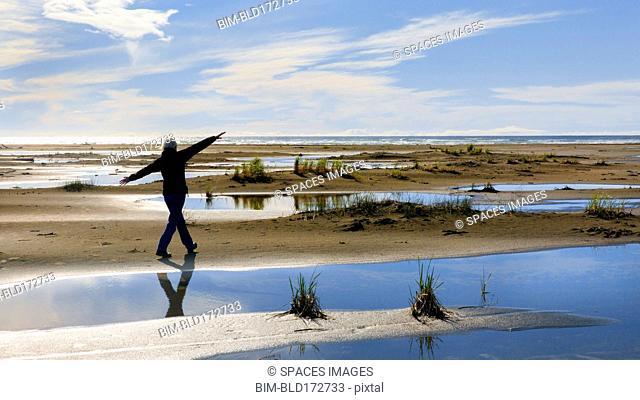 Older woman walking in marshy rural field