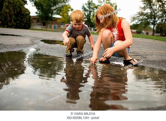 Children playing in puddle on road