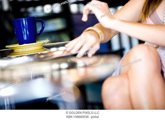 Close-up view of a woman's hands and legs next to a cafi table