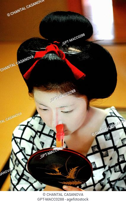 A MAIKO APPRENTICE GEISHA WITH HER TRADITIONAL MAKEUP DORAN. APPLICATION WITH A BAMBOO BRUSH BURASHI OF A PINK MAKE-UP TO MODEL THE FEATURES