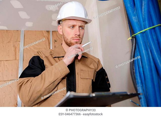 young handsome builder thinking about something while holding clipboard