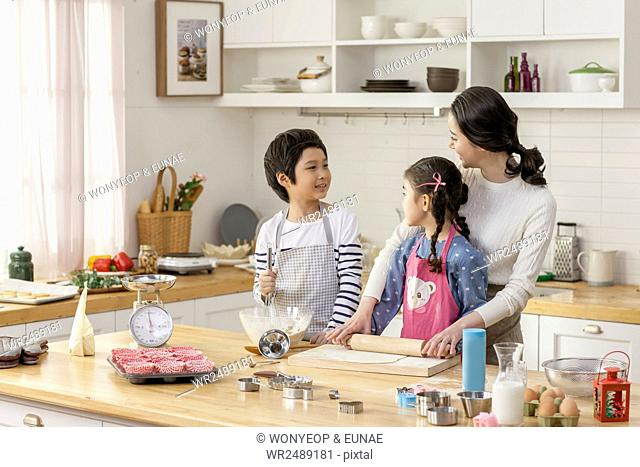 Smiling mother , son and daughter cooking together in kitchen