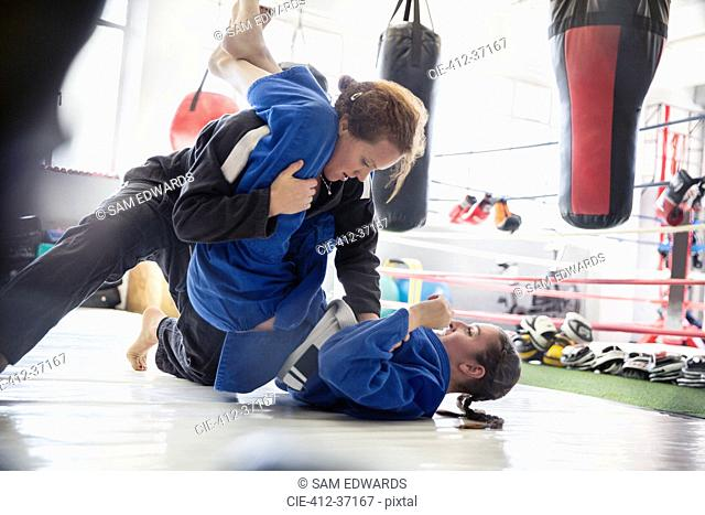 Women practicing judo in gym