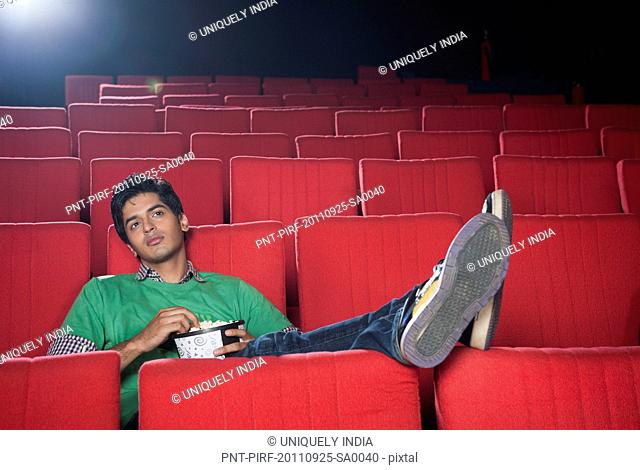 Man watching movie with popcorns in a cinema hall