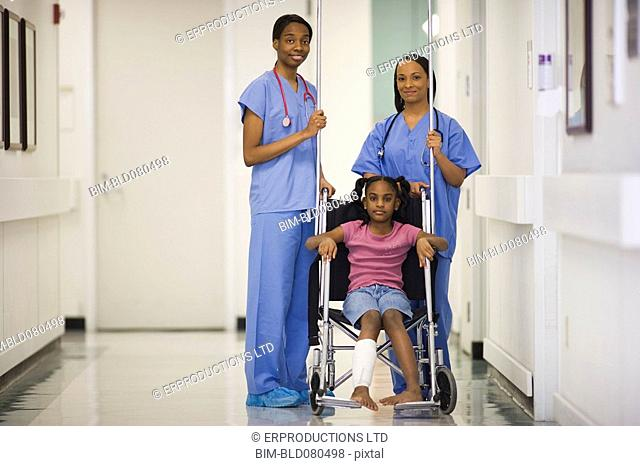 Nurses standing near African American girl in wheelchair