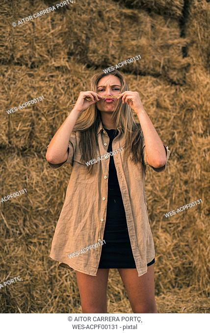 Young woman standing in front of hay bales making moustache with her hair