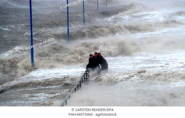 Waves lash the ferry pier, two men hold on a handrail on the North Sea coast in Dagebuell, Germany, 05 December 2013. Storm front Xaver will reach full force on...