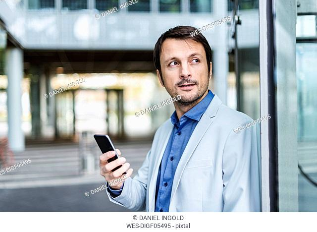 Portrait of a businessman using smartphone in the city