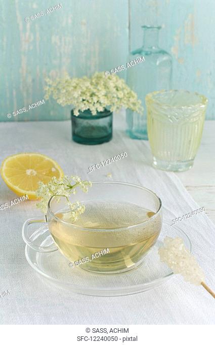 Elderflower tea in a cup, elderflowers, lemon and a rock candy stick