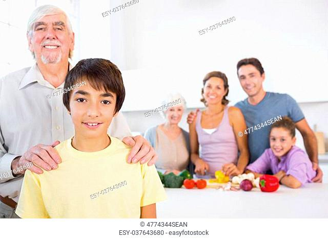 Grandfather and grandson standing beside the kitchen counter with family behind them