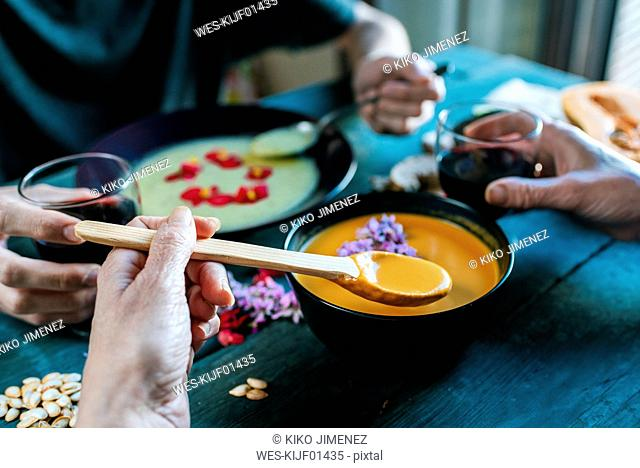 Hand of woman eating creamed pumpkin soup and drinking red wine