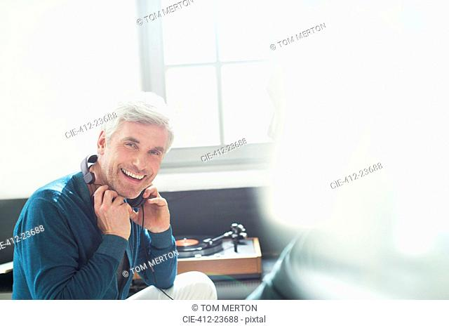 Older man listening to turntable with headphones