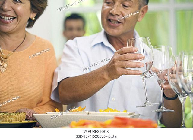 Close-up of a mature woman smiling with a mature man holding two glasses of wine