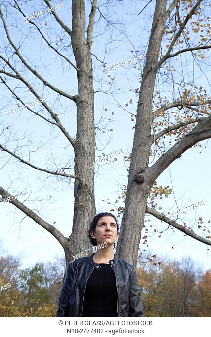 Young woman in a leather jacket standing next to a tree with no leaves