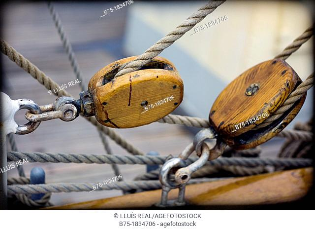 closeup of wooden pulleys, ropes and shackles on deck of sailing boat