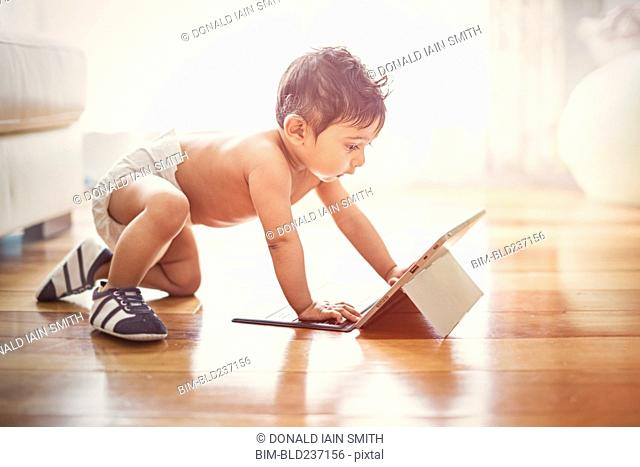 Indian baby boy crawling on floor with digital tablet