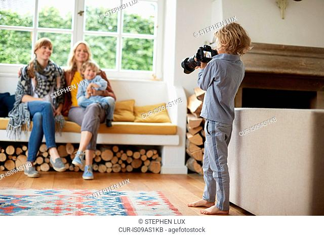 Boy taking photograph of adult women and boy sitting in window seat