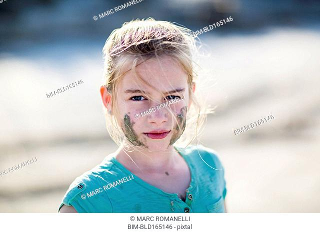 Caucasian girl with messy face on beach