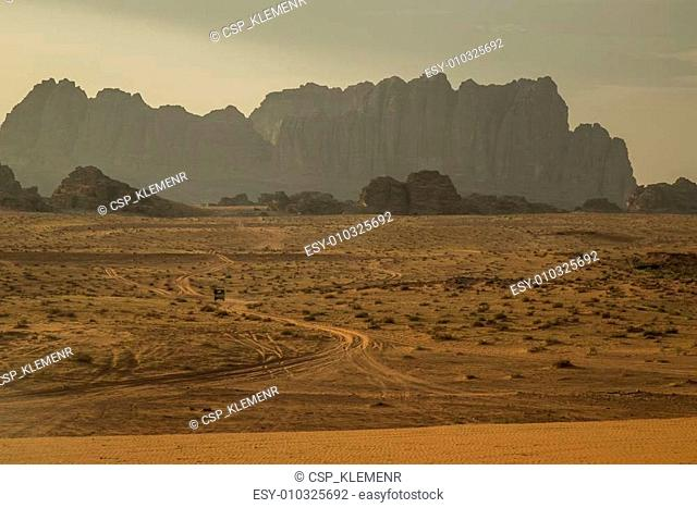 Mountains in Wadi Rum desert with desert road and small car